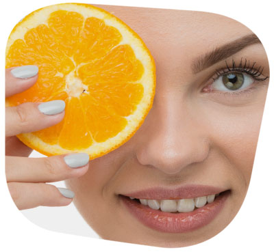 Frau hält Orange vor das Gesicht